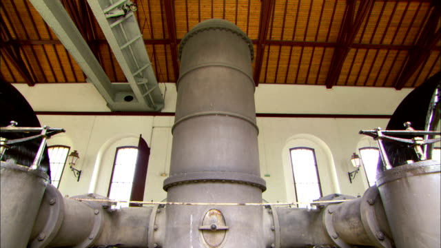 large water wheels turn next to massive pipes in a water pumping station. - pumping station stock videos & royalty-free footage
