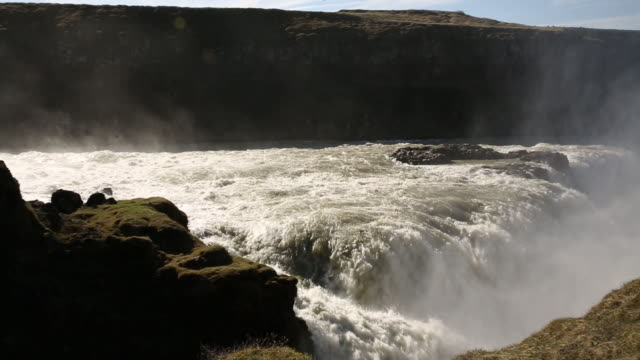 Large waterfall near green pastures in Iceland