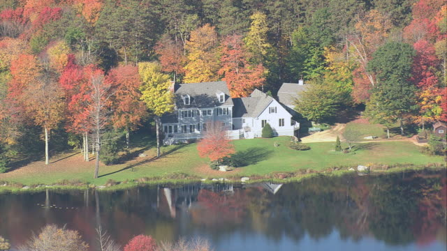 AERIAL Large waterfront home amid fall foliage / Amherst, Massachusetts, United States