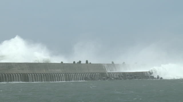 large waves crash into a sea wall at a port in taiwan as typhoon soudelor makes landfall - 突堤点の映像素材/bロール