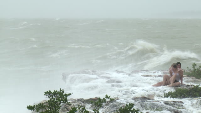 Large waves crash into cliff onto two girls during cyclone Carlos in Darwin.  Girls are not cleared / AUDIO