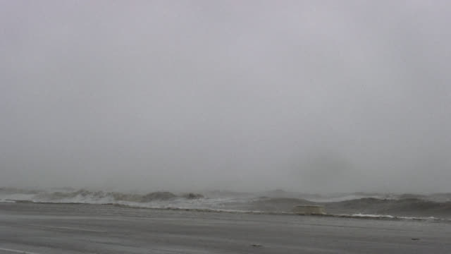 Large waves striking seawall during hurricane.