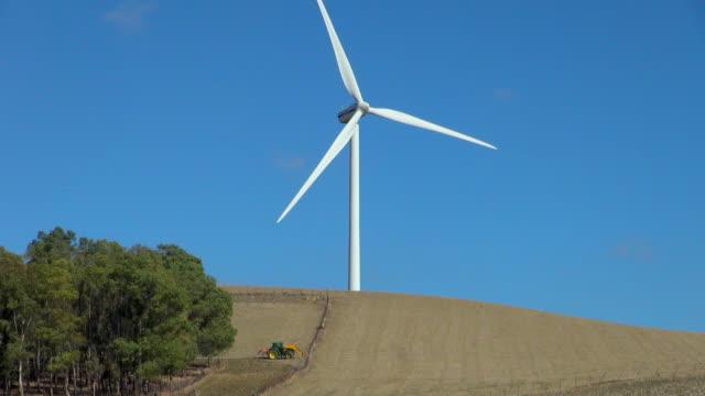 Large Wind Turbine Against a Blue Sky Behind a Farm