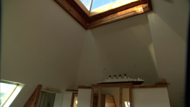 vídeos de stock e filmes b-roll de large windows and a skylight bring sunlight into a living room. - loft apartment