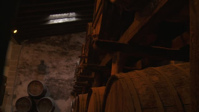 Large wooden barrels hold wine in a cellar in Andalusia.
