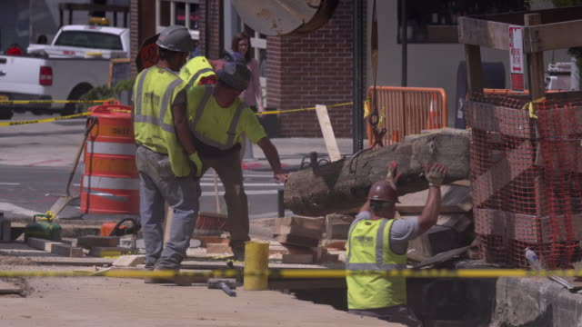 large wooden beam gets lowered beneath the street surface as workers move it into place. - bulldozer stock videos and b-roll footage