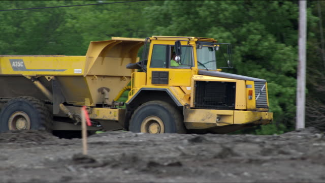 large yellow articulated dump truck driving through construction excavation site towards camera - 1 - dump truck stock videos and b-roll footage