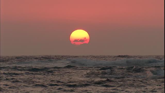 A large yellow sun hangs over the ocean horizon in a grey sky.