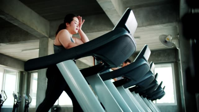 vídeos de stock e filmes b-roll de larger woman exhausted by exercising on treadmill - estilo de vida pouco saudável