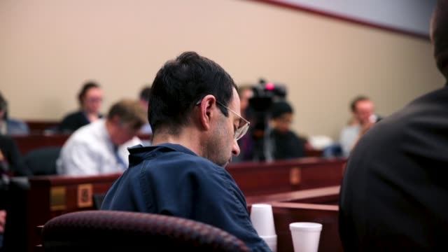larry nassar listens to victim impact statements during his sentencing hearing after being accused of molesting more than 100 girls while he was a... - lansing stock videos and b-roll footage