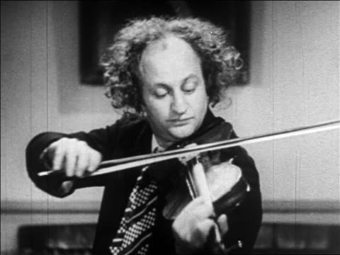 larry of the 3 stooges playing violin with toupee attached to bow / feature - one mid adult man only stock videos & royalty-free footage