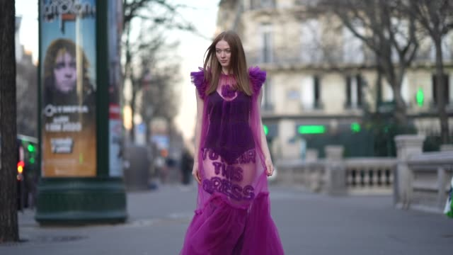"""larsen thompson wears a black bodysuit under a viktor & rolf fuchsia and purple transparent ruffled and gathered dress with a message :"""" i am not... - paris fashion week - haute couture spring/summer 2020点の映像素材/bロール"""