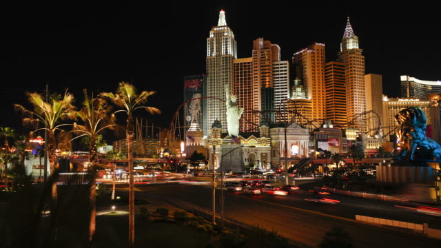 las vegas boulevard traffic moves past palm trees and the intersection by the new york new york casino. - the strip las vegas stock videos & royalty-free footage