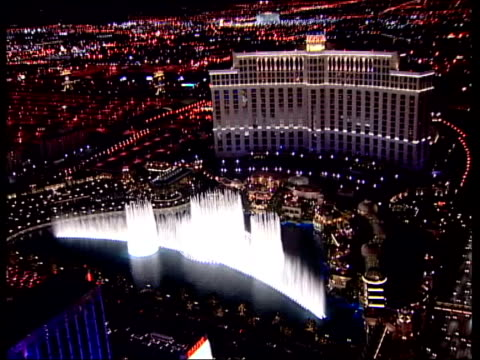 las vegas: ext/night air view fountain and bellagio hotel-casino classic diamond shaped las vegas sign reading 'welcome to fabulous las vegas nevada'... - bellagio hotel stock videos & royalty-free footage