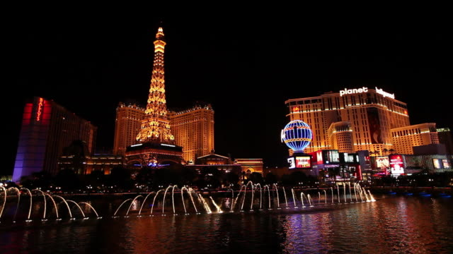 las vegas strip with eiffel tower and fountains at night - replica della torre eiffel video stock e b–roll