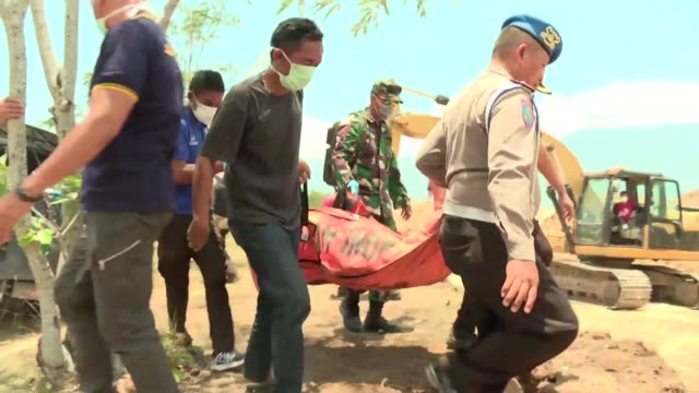 las victimas del sismo y tsunami en indonesia comenzaron a ser enterradas el lunes en inmensas fosas comunes mientras la onu estima que 19100... - natural disaster stock videos & royalty-free footage