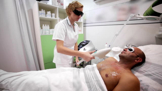 laser hair removal from the patient's chest - chest hair stock videos and b-roll footage