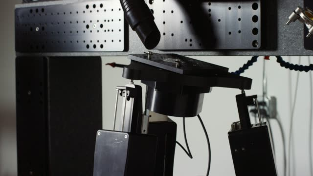 a laser micromachine system rotates and tilts on hydraulic robotic legs in an indoor manufacturing facility - hydraulics stock videos and b-roll footage