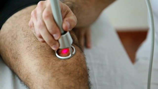 laser physiological therapy on knee - chiropractic adjustment stock videos & royalty-free footage