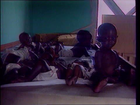 "last ever ""news at ten""; lib zaire: goma: group of rwandan refugee children sitting and lying on bed, following the tutsi massacre of hutus in rwanda - フツ族点の映像素材/bロール"