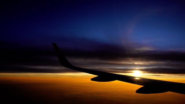 last light from flying airplane flight with aircraft wing and flare of sunrise sunset - aircraft wing stock videos & royalty-free footage