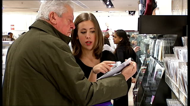 vidéos et rushes de last minute christmas shoppers on london's oxford street **music heard sot** various of men and women browsing in lingerie department of selfridges - underwear