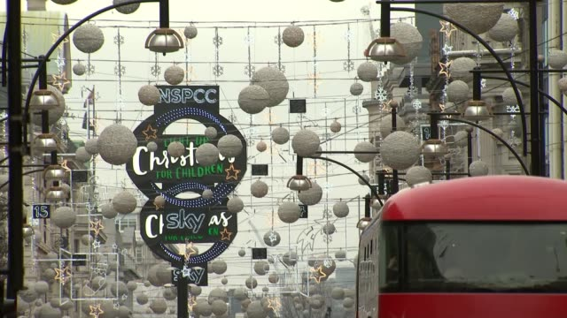 London Oxford Street EXT Shoppers along on Christmas Eve Christmas lights and decorations on Oxford Street TILT DOWN double decker buses and taxi...