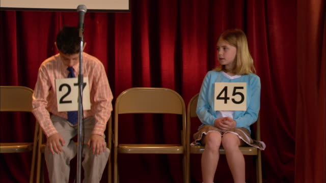 Last two finalists sitting on stage in spelling bee / boy walking up to microphone / zoom in to boy nervously spelling word / Los Angeles, California