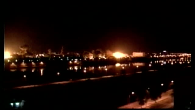 barack obama speech lib baghdad buildings exploding into flames and smoke rising into air during 'shock and awe' bombing of baghdad by us forces night - 2003 stock-videos und b-roll-filmmaterial