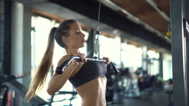 lat pull down exercise at gym, 4k. - grimacing stock videos and b-roll footage
