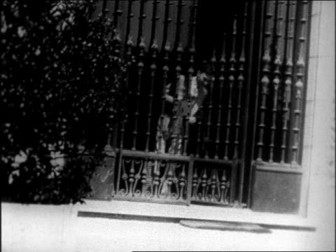 b/w late 1920s mayor jimmy walker poking head out of gates at san simeon estate / documentary - one mid adult man only stock videos & royalty-free footage