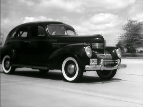 b/w late 1930s/early 1940s tracking shot black car driving on highway - zweispurige strecke stock-videos und b-roll-filmmaterial