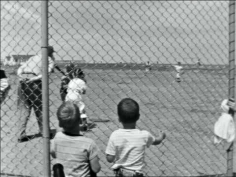 late 1950s batter swinging at + missing ball in little league game / boys watching at fence - youth baseball and softball league stock videos and b-roll footage