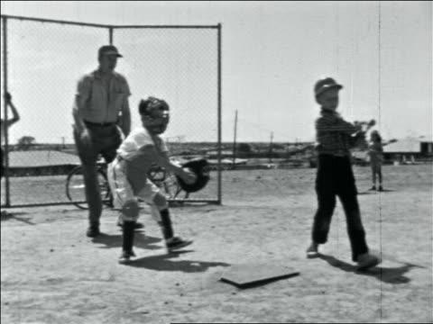 vídeos y material grabado en eventos de stock de late 1950s batter swinging at + missing ball / umpire signals strike / catcher throws ball - bate de béisbol