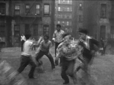 b/w late 1950s boys throwing football + running past camera in empty philadelphia lot / documentary - reporterstil stock-videos und b-roll-filmmaterial