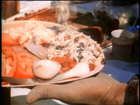 late 1950s close up man's hands putting food on full paper plate at picnic / newsreel - paper plate stock videos & royalty-free footage