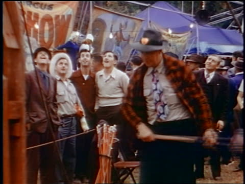 Late 1950s man in hat + plaid jacket hitting Test Your Strength game with hammer / newsreel