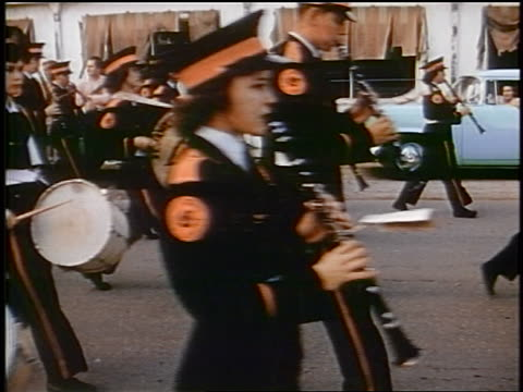 late 1950s men + women in uniforms in marching band passing camera in parade / newsreel - marching band stock videos and b-roll footage