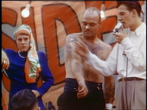 late 1950s shirtless tattooed man standing next to man talking into microphone / carnival - shirtless stock videos & royalty-free footage