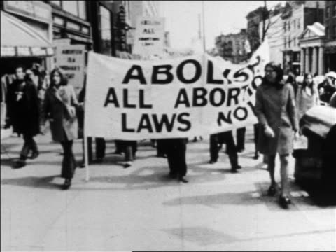 B/W late 1960s women marching with 'Abolish All Abortion Laws Now' banner / newsreel