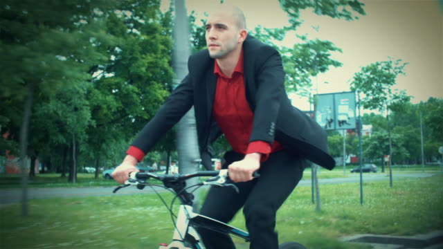 Late 20's businessman riding a bike to work.
