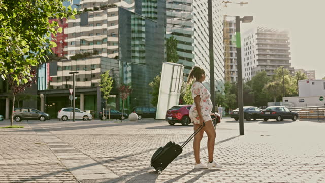 late 20s pregnant hispanic traveler pulling wheeled luggage - maternity wear stock videos & royalty-free footage