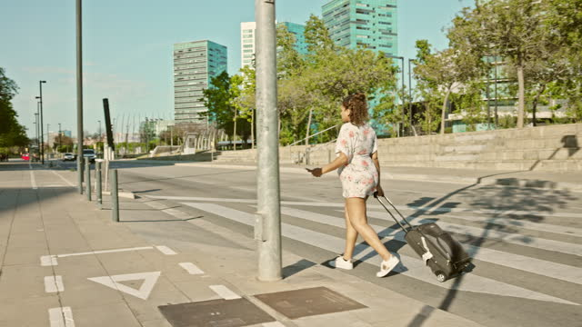 late 20s pregnant tourist crossing city street with suitcase - maternity wear stock videos & royalty-free footage