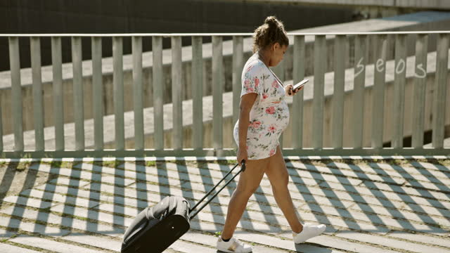 late 20s pregnant tourist with suitcase checking smart phone - maternity wear stock videos & royalty-free footage