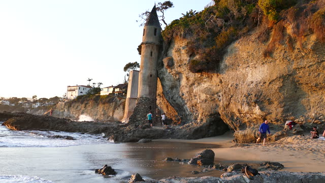 late afternoon people sitting on the sand, walking, taking photos of the ocean by a 60 foot tower next to a cliff on victoria beach, southern... - laguna beach california stock videos & royalty-free footage