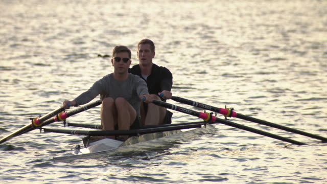 late afternoon sun close up of two men sitting in a scull boat they start rowing and camera pans back to wide view of them against the melbourne city... - ウォータースポーツ点の映像素材/bロール