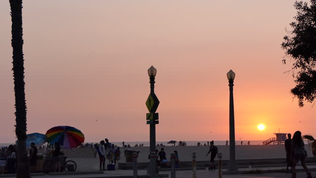 vidéos et rushes de late afternoon the sun is setting with a bright orange and red sky, people and beach umbrellas on the sand, people by a rolling food concession stand... - allée couverte de planches