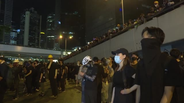 late into the evening hundreds of masked protesters mill outside the government headquarters chanting slogans after hundreds of thousands of... - hong kong island stock videos & royalty-free footage