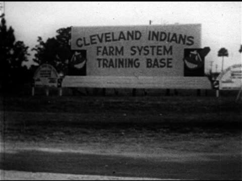 vídeos de stock e filmes b-roll de late model four door sedan passing 'cleveland indians farm system training base' sign ms rookie outfielder jim lemon walking from car ws clubhouse ws... - camisola de basebol