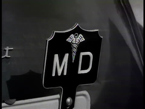 late model sedan parked at curb in front of neighborhood twostory house md medical tag on license plate w/ caduceus brunette woman knocking entering... - caduceus stock videos and b-roll footage